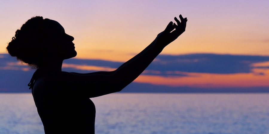 persona orando en el atardecer